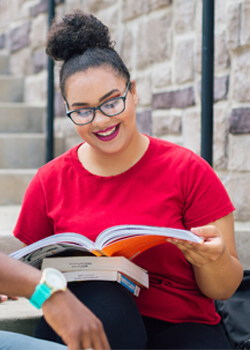 Female student looking at text books sitting on outside step