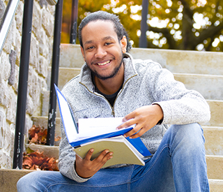 Photo of a male student holding a book while sitting down on campus steps mobile image