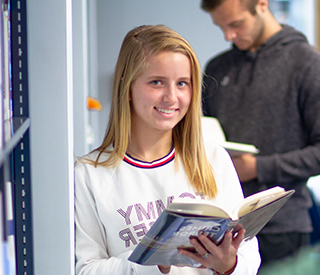Female student with book in the library mobile image
