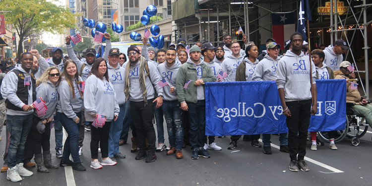 Group of Berkeley students at 老兵 Day Parade in NYC holding Berkeley College flag